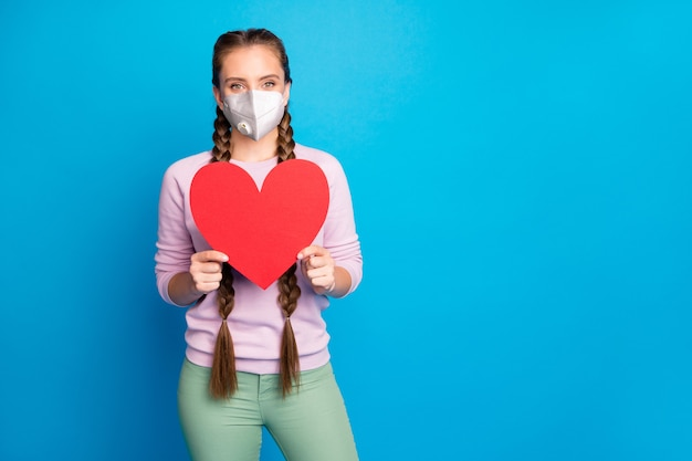 Portrait of her she nice attractive healthy girl wearing safety n95 mask holding in hand card stop heart sickness illness mers cov prevention isolated bright vivid shine blue color background
