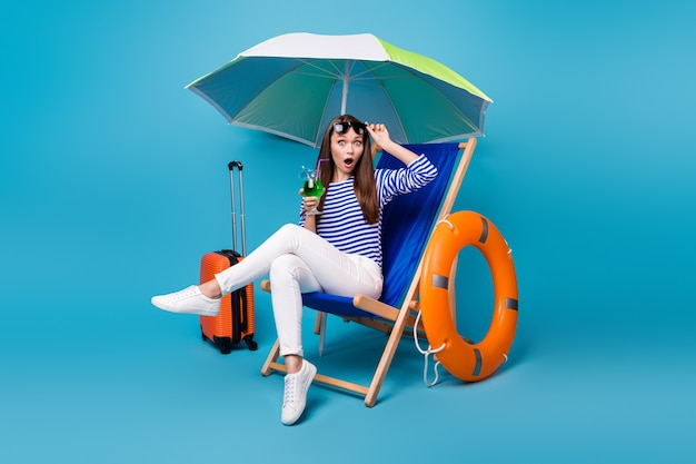 Portrait of her she nice attractive lovely amazed funky girl sitting in chair under parasol drinking mojito rest relax exotic tour isolated bright vivid shine vibrant blue color background