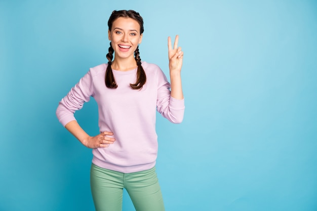 Portrait of her she nice attractive lovely charming feminine cheerful cheery girl showing v-sign weekend isolated bright vivid shine vibrant blue green teal turquoise color