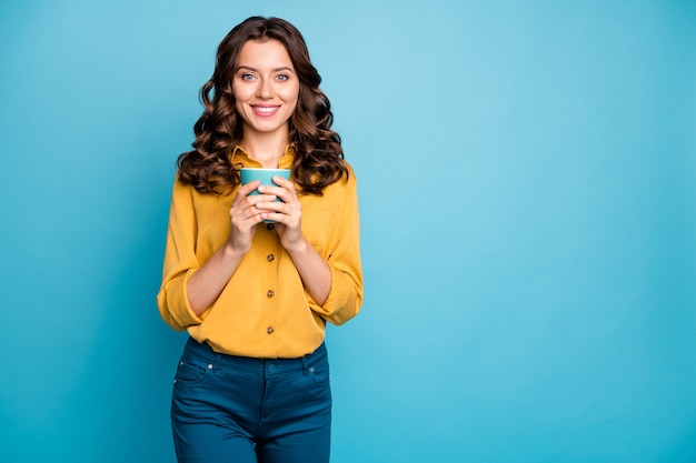 Portrait of her she nice attractive lovely charming pretty cheerful cheery wavy-haired girl holding in hands cup of tea .