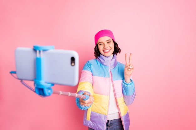 Portrait of her she nice attractive lovely cheerful cheery funky girlfriend taking making selfie showing v-sign free time social influencer isolated over pink pastel background