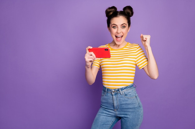 Portrait of her she nice attractive lovely cheerful cheery girl fan watching tv television sport match having fun isolated on bright vivid shine vibrant lilac violet purple color background