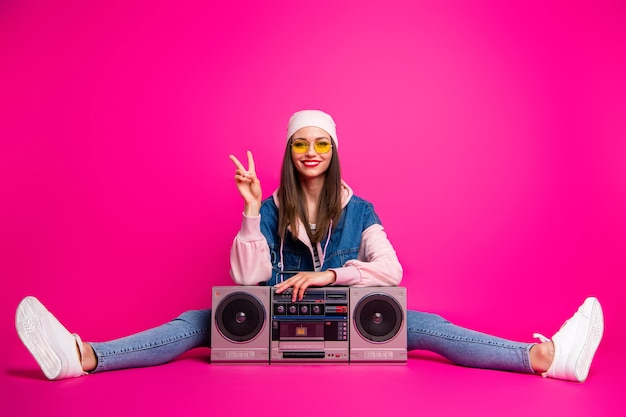 Portrait of her she nice attractive lovely cheerful cheery glad girl sitting next to boom-box showing v-sign twine isolated on bright vivid shine vibrant pink fuchsia color