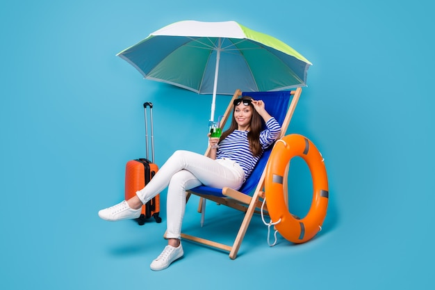 Portrait of her she nice attractive lovely cheerful girl sitting in chair drinking mojito chill relax exotic tour destination abroad isolated bright vivid shine vibrant blue color background