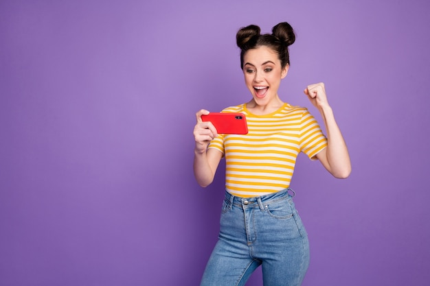 Portrait of her she nice attractive lovely focused cheerful cheery girl playing device watching tv sport show having fun isolated on bright vivid shine vibrant lilac violet purple color background