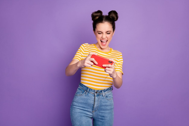 Portrait of her she nice attractive lovely pretty addicted cheerful cheery girl playing device battle having fun isolated on bright vivid shine vibrant lilac violet purple color background
