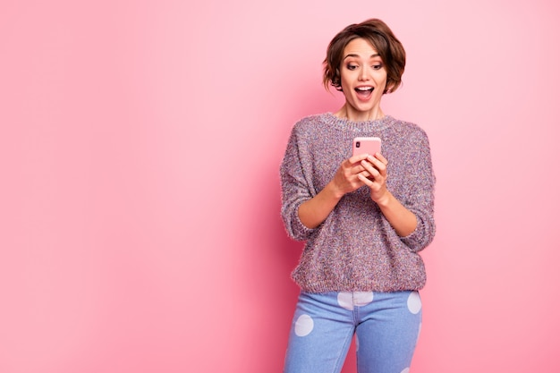 Portrait of her she nice attractive lovely pretty winsome charming cute cheerful cheery glad brown-haired girl using cell fast speed connection isolated over pink pastel color wall