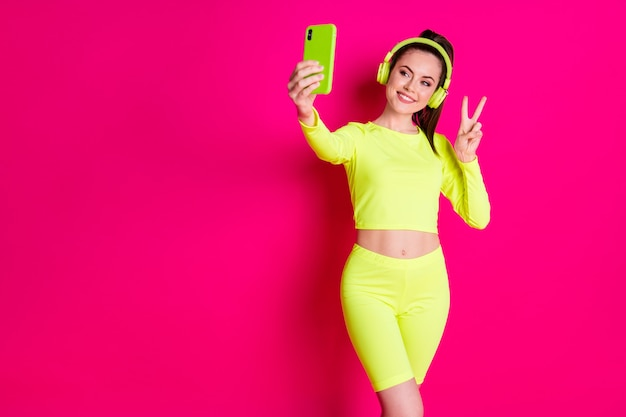 Portrait of her she nice attractive pretty charming cheerful cheery glad girl listening music taking selfie showing v-sign isolated bright vivid shine vibrant pink fuchsia color background