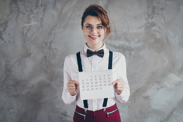 Portrait of her she nice attractive pretty lovely charming cheerful cheery wavy-haired girl holding in hands paper calendar planner isolated on gray concrete industrial wall background