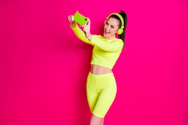 Portrait of her she nice attractive pretty lovely cheerful cheery girl listening music pop melody making taking selfie having fun isolated bright vivid shine vibrant pink fuchsia color background