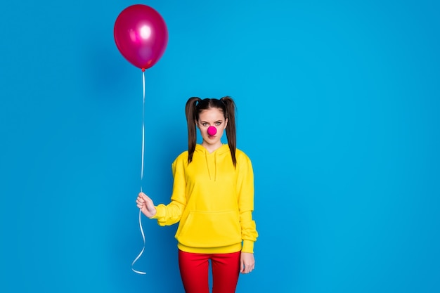 Portrait of her she nice attractive sad bored sullen gloomy girl circus clown holding in hand helium ball dull event occasion isolated over bright vivid shine vibrant blue color background