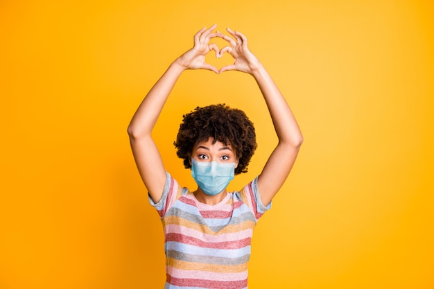 Portrait of her she nice healthy wavy-haired girl wearing safety gauze mask showing heart shape medicine social distance isolated bright vivid shine vibrant yellow color background
