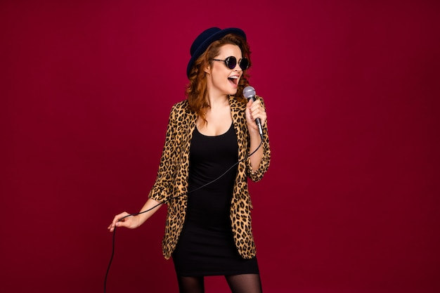 Portrait of her she nice-looking attractive fashionable lovely cheerful cheery wavy-haired girl singing romance pop single hit isolated on red maroon burgundy marsala color background