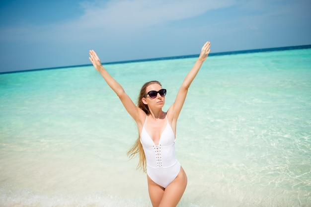 Portrait of her she nice-looking attractive fit thin slender healthy lady resting famous luxury resort tour destination enjoying sunny weather azure clean clear sea fresh air rising hands up