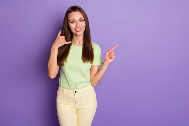 Portrait of her she nice-looking attractive lovely cheerful cheery girl showing call me mobile phone sign copy space advert isolated over bright vivid shine vibrant lilac violet color background