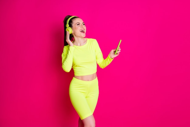 Portrait of her she nice-looking attractive lovely glad cheerful cheery sporty girl listening music singing having fun isolated over bright vivid shine vibrant pink fuchsia color background