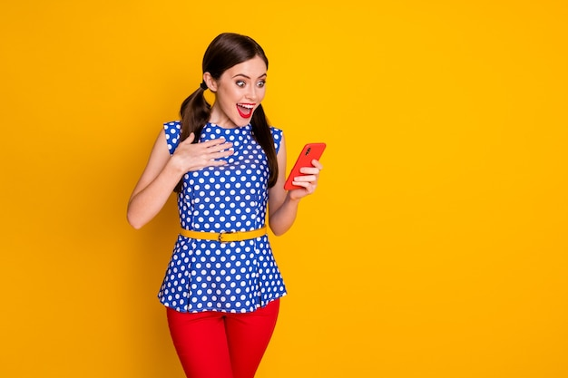 Portrait of her she nice-looking attractive pretty delighted cheerful cheery girl using cell app 5g reading comment feedback isolated bright vivid shine vibrant yellow color background
