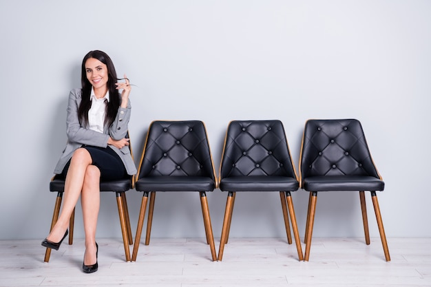 Portrait of her she nice-looking attractive pretty elegant cheerful lady partner leader economist marketer sitting in chair expecting meeting isolated light pastel gray color background