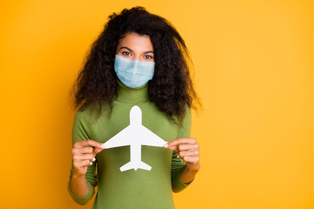 Portrait of her she nice wavy-haired girl wearing safety gauze mask stop wuhan mers cov influenza holding in hand paper plane isolated bright vivid shine vibrant yellow color background