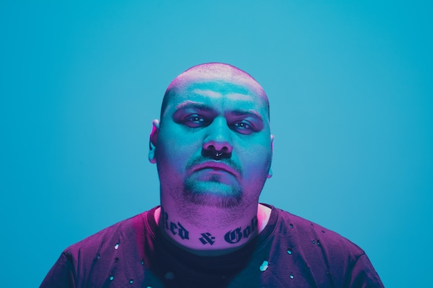 Portrait of a hipster guy with colorful neon light on blue background