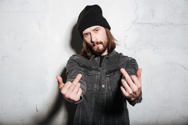 Portrait of a hipster man in hat showing fuck you sign isolated over wall