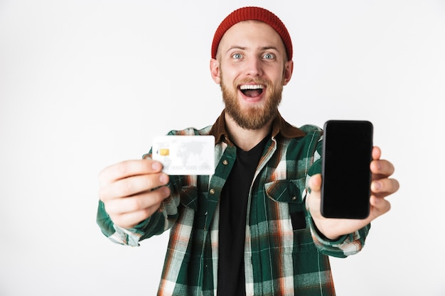 Portrait of hipster man holding credit card and cell phone, while standing isolated over white background