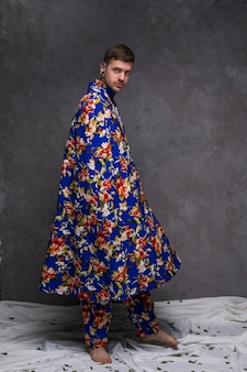 Portrait of a hipster young man with floral drape looking at camera against grey wall
