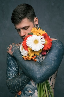 Portrait of a hipster young man with tattooed on his body embracing the gerbera flowers