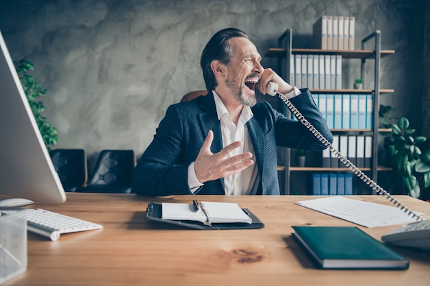 Portrait of his he depressed crazy desperate jobless guy qualified expert talking yelling on phone scandal fail at modern loft industrial style interior workplace workstation