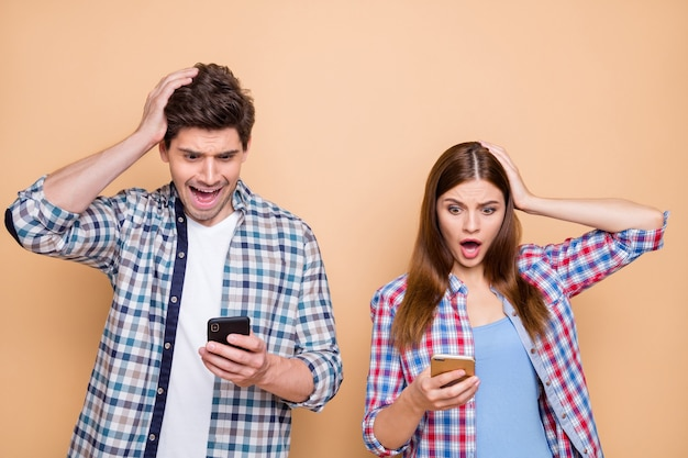Portrait of his he her she nice attractive charming amazed worried puzzled couple wearing checked shirt using cell browsing feednews media isolated over beige pastel color background