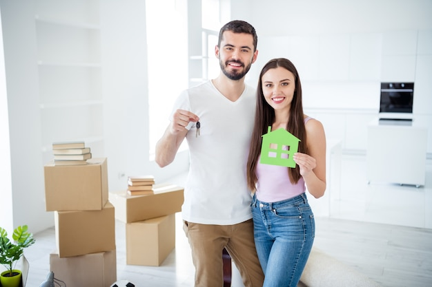 Portrait of his he her she nice attractive cheerful cheery couple embracing holding in hands key green house figure purchase trust bank loan at space flat light white interior house indoors