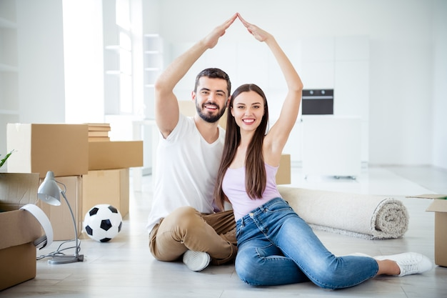 Portrait of his he her she nice attractive cheerful cheery couple sitting on floor making roof over head life insurance investment at space flat light white interior house accommodation