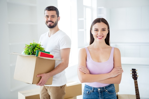 Portrait of his he her she nice attractive cheerful glad confident couple packing belongings carrying fresh start at new place space studio flat accommodation light white interior house