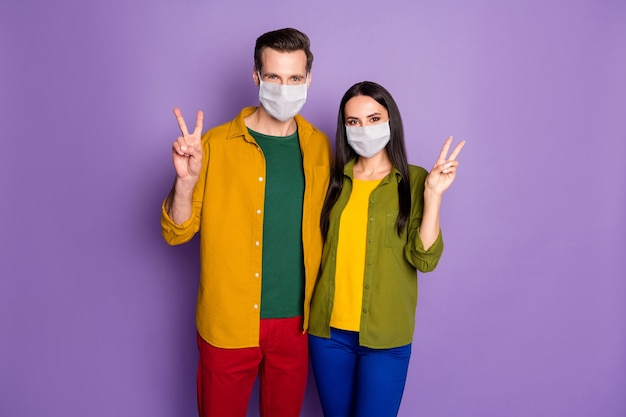 Portrait of his he her she nice attractive healthy couple wearing safety mask health care embracing stop pandemia mers cov preventive measures stay home isolated violet purple color background