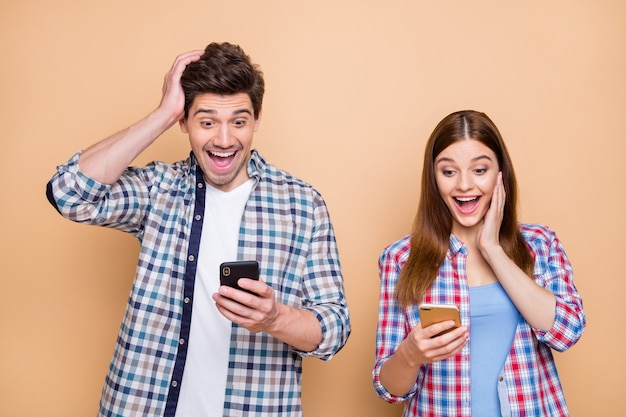 Portrait of his he her she nice attractive lovely amazed wondered cheerful couple wearing checked shirt using cell watching smm media subscription isolated over beige pastel color background