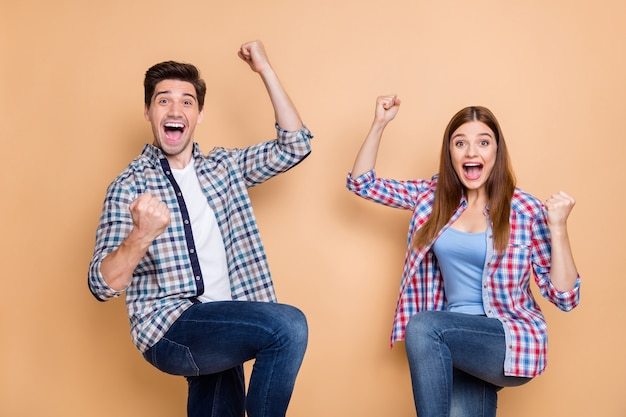 Portrait of his he her she nice attractive lovely charming ecstatic cheerful cheery couple wearing checked shirt rejoicing great luck isolated over beige pastel color background