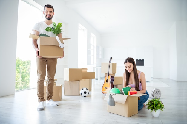 Portrait of his he her she nice attractive lovely cheerful cheery couple packing unpacking stuff unwrapping rental open space flat light white interior house accommodation