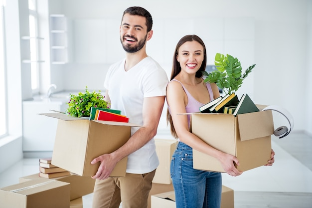 Portrait of his he her she nice attractive lovely cheerful cheery glad couple carrying stuff package holding in hands boxes at new place space flat light white interior house household indoors