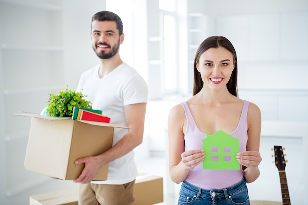 Portrait of his he her she nice attractive lovely cheerful confident couple carrying stuff package holding in hands house card at new place space studio flat light white interior house indoors