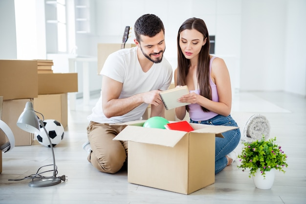 Portrait of his he her she nice attractive lovely cheerful focused couple buyers packing belongings things stuff writing list at open space flat light white interior house accommodation investment