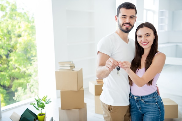 Portrait of his he her she nice attractive lovely cheerful married spouses embracing holding in hands key rent bank purchase space building development at flat light white interior