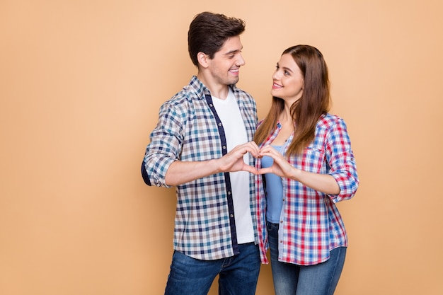 Portrait of his he her she nice attractive lovely tender sweet gentle cheerful couple wearing checked shirt showing heart figure honey moon isolated over beige pastel color background