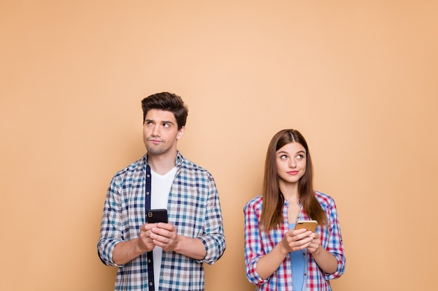 Portrait of his he her she nice attractive minded pensive couple wearing checked shirt creating new post smm internet online media isolated over beige pastel color background