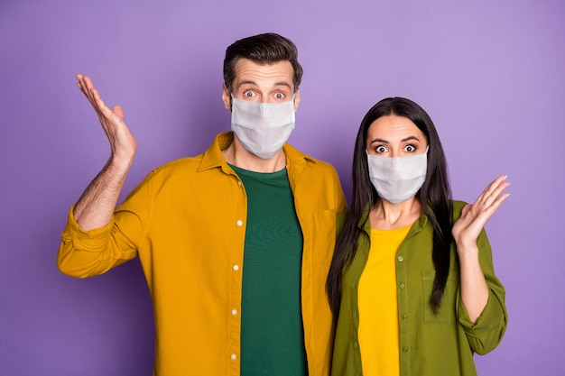 Portrait of his he her she nice attractive scared afraid couple wearing safety mask health care embracing stop pandemia influenza flue grippe novelty isolated violet purple color background