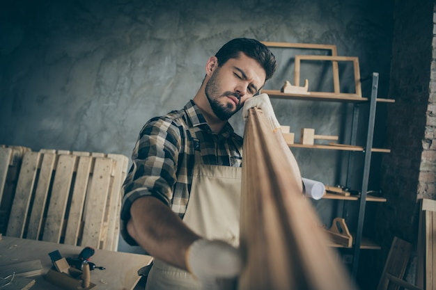 Portrait of his he nice attractive bearded serious focused concentrated experienced skilled guy specialist expert looking checking smoothness plank at modern industrial loft style interior