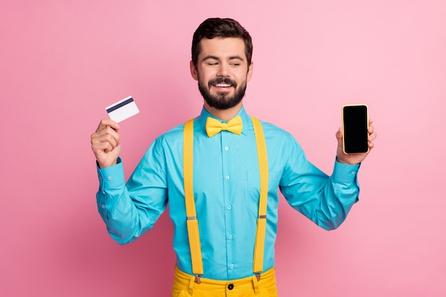 Portrait of his he nice attractive cheerful cheery confident bearded guy wearing mint blue shirt holding in hands cell bank card online pay app isolated over pastel pink color background