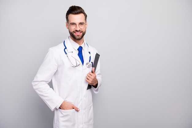 Portrait of his he nice attractive cheerful cheery doc wearing formalwear physician holding in hand document clipboard isolated on light white gray pastel color