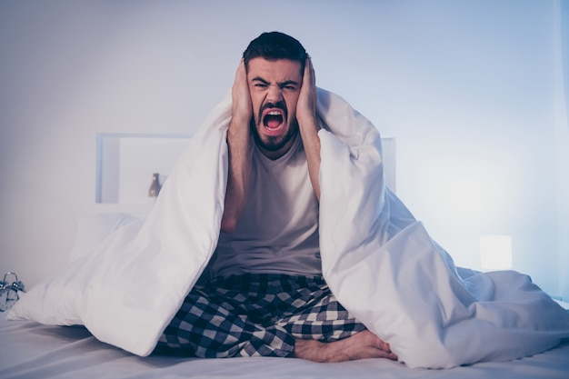 Portrait of his he nice attractive crazy mad frustrated exhausted depressed bearded guy sitting on bed suffering from insomnia covered in blanket at night late evening home dark room flat house