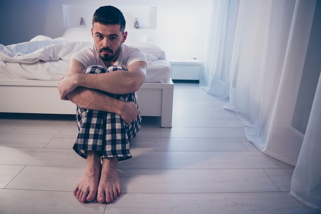 Portrait of his he nice attractive depressed guy sitting on floor suffering from insomnia bad unpleasant feelings at night late evening home illuminated room flat house