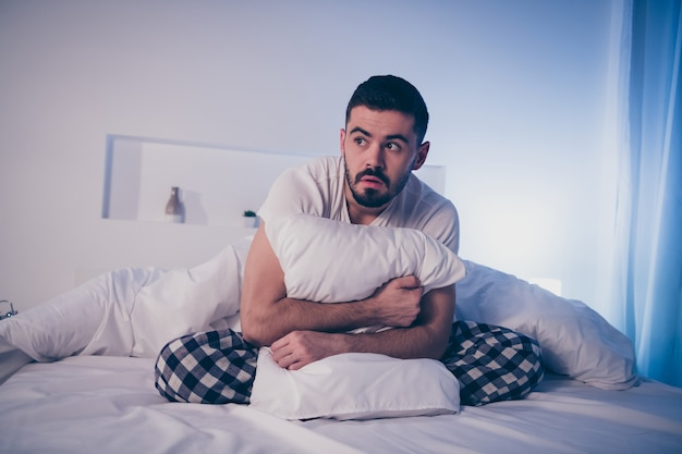 Portrait of his he nice attractive depressed scared guy sitting on bed suffering from insomnia bad time at night late evening home illuminated room flat house